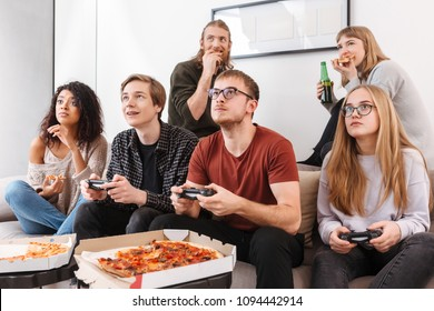 Group of thoughtful friends sitting on sofa and spending time together while playing video games,eating pizza and drinking beer at home