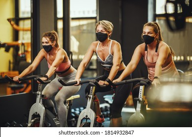 Group of thre fit female friends with protective mask having sports training on exercise bikes in a gym during Covid-19 pandemic.