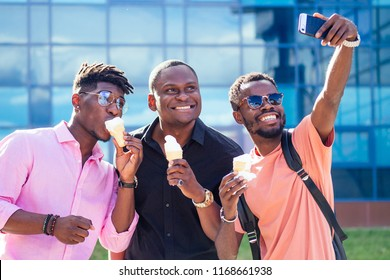 a group of three African American guy eating ice cream in a waffle horn in the summer in the park