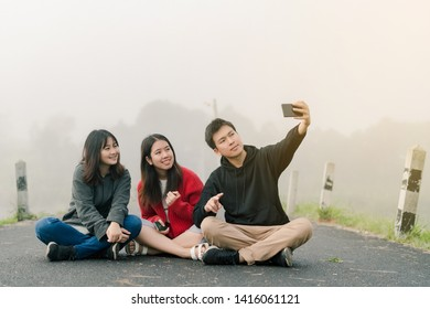 A group of three Asian friends wearing a sweater using a selfie phone to take pictures in a tourist attraction. Along the road beside the reservoir in the thick fog With a smiling   happiness