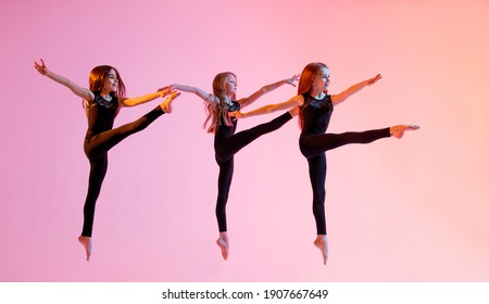 group of three ballet girls in black tight-fitting suits jumping on a red background with their long hair down.