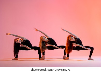 group of three ballet girls in black tight-fitting suits dancing on a red background with their long hair down.