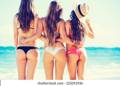 Group of Three Beautiful Hot Young Women on the Beach in Small Bikinis, Rear View of Sexy Butts