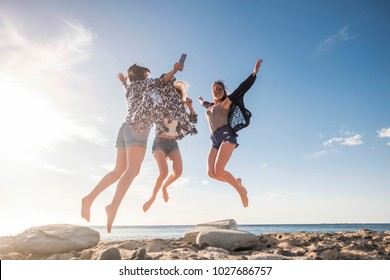 Group of three beautiful nice young woman jumping for fun and happiness, independent life together in friendship. Tenerife stone beach in a sunny day, enjoy the time.