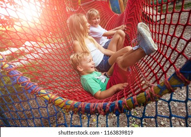 Group of three blond scandinavian children siblings having fun in red net tunnel in playground or amusement park. Holiday friendship and happy childhood concept.