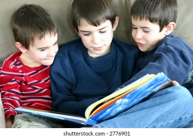 A group of three boys reading a book together
