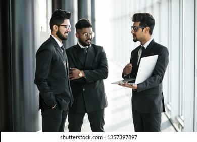Group of three business man in suits looking at laptop standing in modern office hall at informal meeting