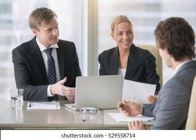 Group of three business partners discussing new project at meeting in office room, using laptop. Businesspeople in formal wear suits interacting, brainstorming. City office building on the background
