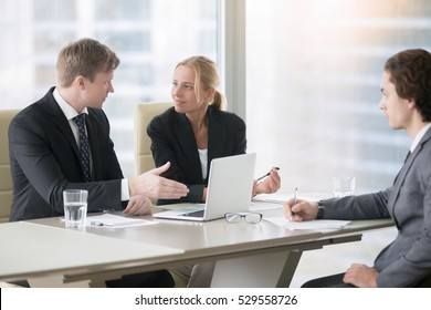 Group of three business partners discussing new project at meeting in office room, using laptop. Businesspeople in formal wear suits interacting, brainstorming. Urban office building on the background