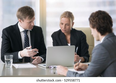 Group of three business partners discussing new project at meeting in office room, using laptop. Businesspeople in formal wear suits interacting, brainstorming, looking presentation on laptop screen