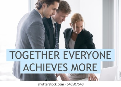 """Group of three business partners discussing new project at meeting in office room, using laptop. Business concept. Photo with motivational text """"Together everyone achieves more"""""""
