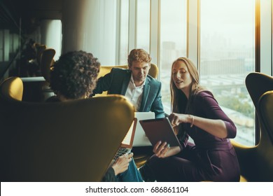 Group of three business people having work meeting on high floor of skyscraper in luxury office interior: caucasian handsome boss looking at screen of digital tablet shown by his female colleague