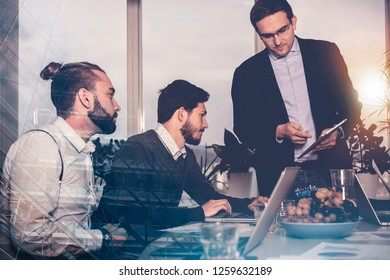 group of three businessmen discussing market approach and lifecycle management of innovative product. standing manager reports to leading decision makers. reflex shot through modern glazing facade