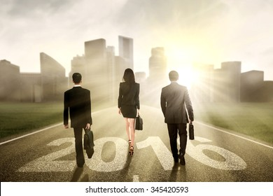Group of three businesspeople walking together on the road with numbers 2016 toward the city