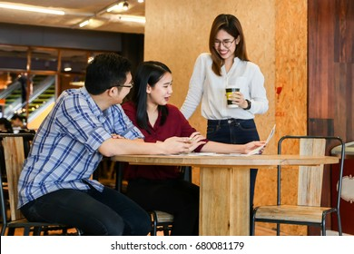 Group of three casual business meeting to discuss ideas in coffee shop.