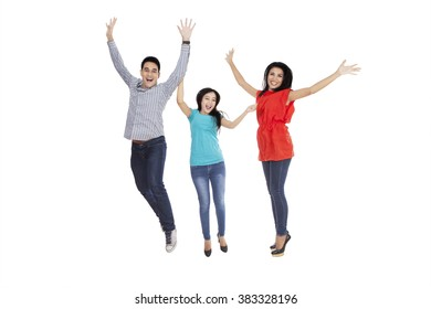 Group of three cheerful people jumping together in the studio, isolated on white background
