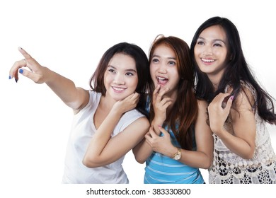 Group of three cheerful teenage girls looking at copy space in the studio, isolated on white background