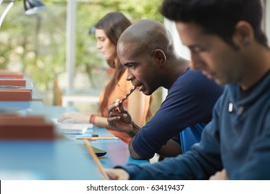 group of three college students studying in library, one of them eating a snack. Horizontal shape, side view, waist up, copy space