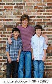 Group of three cute boys standing together against a red brick wall outdoors.