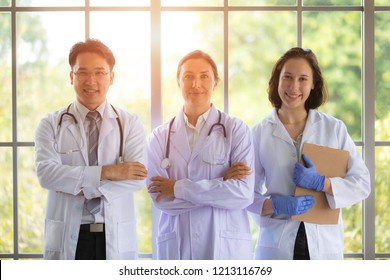 Group of three doctors standing near big window with sunlight in behind. Concept for team work in hospital and healthcare business.