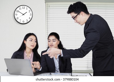 Group of three entrepreneurs discussing in the office while using laptop and planning work
