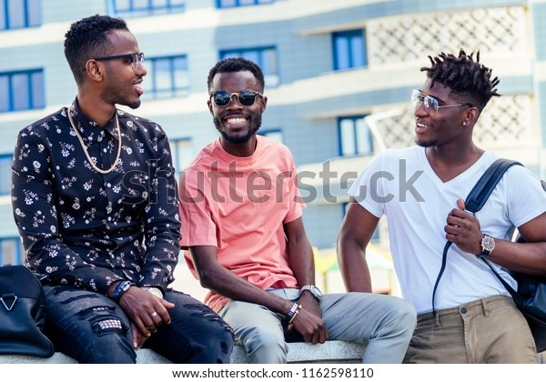 a group of three fashionable cool African American guys students communicating on the street