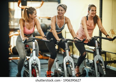 Group of three fit female friends having sports training on exercise bikes in a gym.
