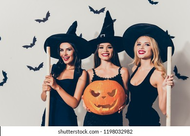 Group of three flirty coquettes in masquerade elegant dresses, with red lips, cutted decorative jack-o-lantern, in dark headwear, on white wall`s background with scary small creatures vampires