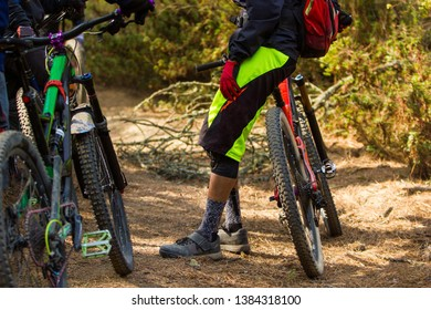 a group of three friends chatting while taking rest during a cycling ride in the forest