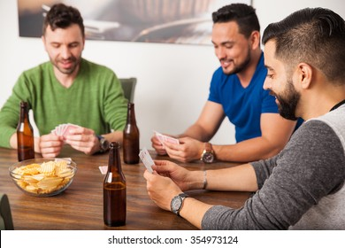 Group of three friends having some fun playing cards and drinking beer at home