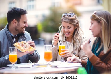 Group of three friends using phone in outdoor cafe on sunny day, eating pizza