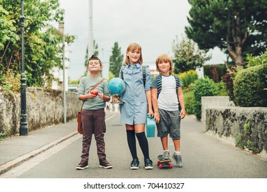 Group of three funny kids wearing backpacks walking back to school. Girl and boys enjoying school activities. Globe, lunch box, red apple and skateboard accessories.