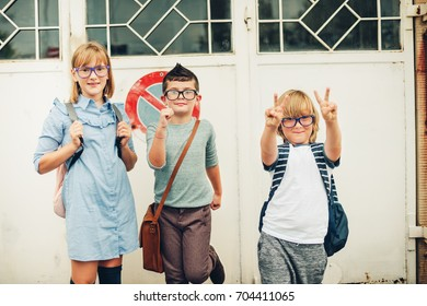 Group of three funny kids wearing backpacks walking back to school. Girl and boys wearing eyeglasses posing outdoors