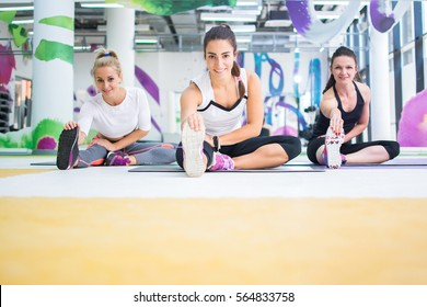 Group of three girls doing exercises in the gym.