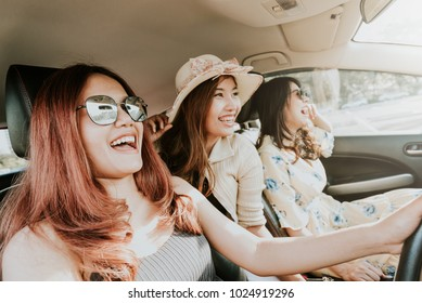 Group of three happy Asian girl best friends traveler laughing and smiling in car during a road trip to vacation.