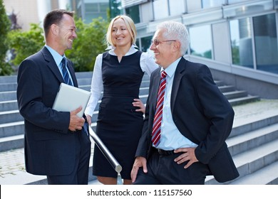 Group of three happy business people discussing a deal outside