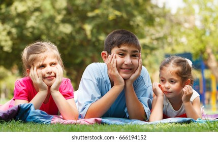 Group of three happy children lying on the grass