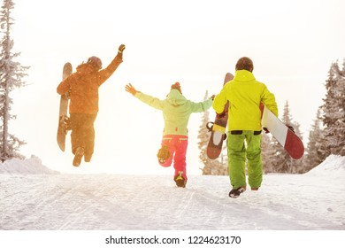 Group of three happy friends snowboarders are having fun and runs to ski slope with snowboards