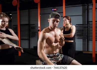 Group of three happy muscular female and male adults sitting together on box as good friends in gym with large speaker in background after a difficult workout session.