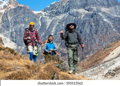 Group of three Hikers of different Age and Ethnicity walking on Footpath in Mountains