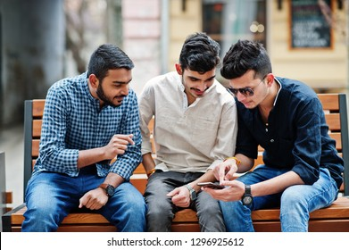 Group of three indian ethnicity friendship togetherness mans. Technology and leisure, guys with phones, sitting on bench.