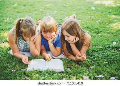 Group of three kids lying on green grass and reading story book together. Education for children