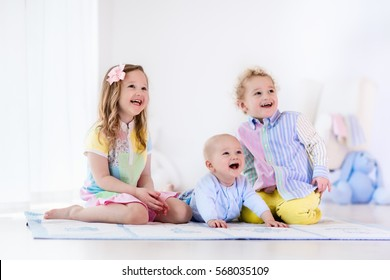 Group of three kids playing in a white bedroom. Children play at home. Preschooler girl, toddler boy and baby in nursery. Happy little brothers and sister bonding having fun together. Siblings love