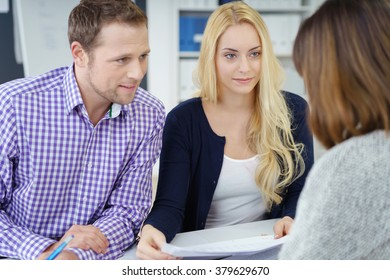 Group of three male and female cheerful young adult workers discussing notes in office during meeting