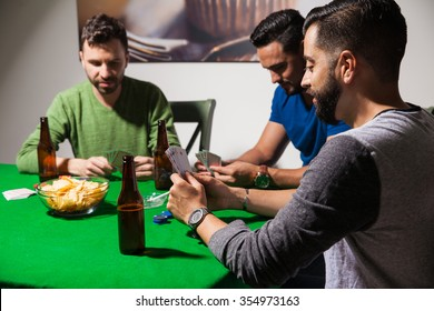 Group of three male friends drinking beer and eating snacks while playing some poker at night