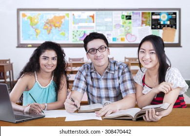 Group of three mixed race student studying together in the class and smiling at the camera