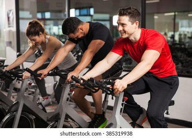 Group of three people enjoying their spinning session at the gym and smiling