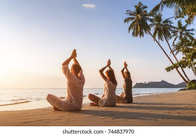 Group of three people practicing yoga lotus position on the beach for relaxation and wellbeing, warm tropical summer landscape with palm trees
