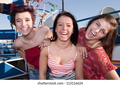 Group of three pretty teenage girlfriends at an amusement park