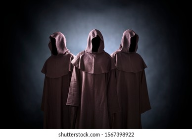 Group of three scary figures in hooded cloaks